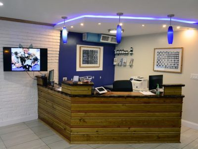 The front desk and reception area for the clinic. The front area is decorated in wood, white and blue